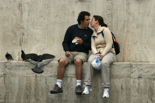 Couple kissing on ledge with pigeons